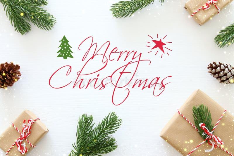 Kerstmisachtergrond met denneappels, spartakken en giften over houten witte achtergrond Vlak leg, hoogste mening royalty-vrije stock fotografie