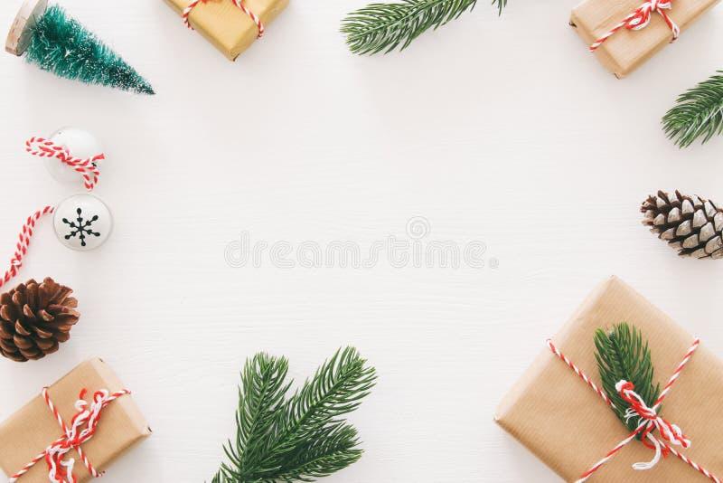 Kerstmisachtergrond met denneappels, spartakken en giften over houten witte achtergrond Vlak leg, hoogste mening stock foto's