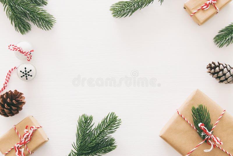 Kerstmisachtergrond met denneappels, spartakken en giften over houten witte achtergrond Vlak leg, hoogste mening royalty-vrije stock foto's