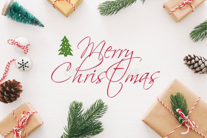 Kerstmisachtergrond met denneappels, spartakken en giften over houten witte achtergrond Vlak leg, hoogste mening stock afbeeldingen
