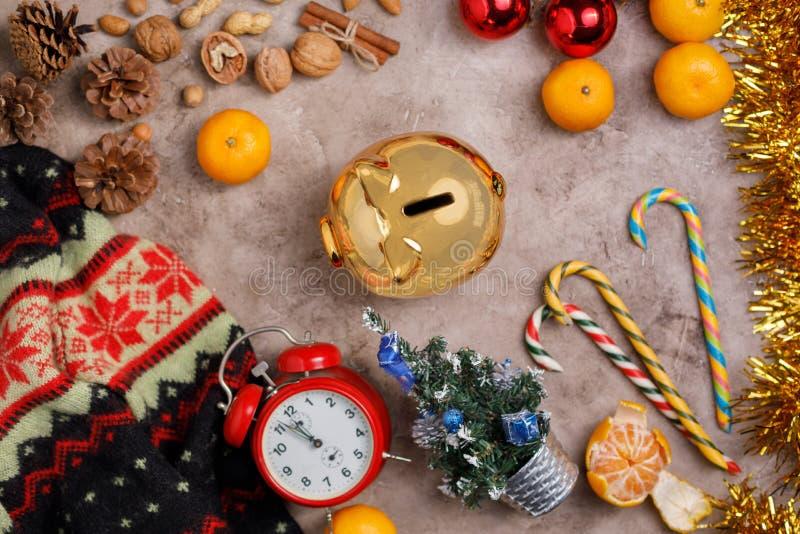 Kerstmisachtergrond met een klok en een gouden spaarvarken, snoepjes, Kerstmisballen en mandarijnen stock foto's