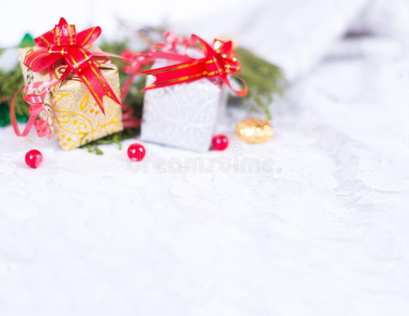 Kerstmisachtergrond met een rood ornament, een gouden giftdoos, bessen en spar in sneeuw royalty-vrije stock foto