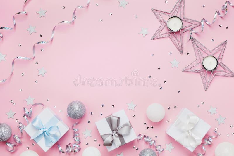 Kerstmisachtergrond met exemplaarruimte voor groettekst Giftvakjes en decoratie op de roze mening van de lijstbovenkant Vlak leg stock fotografie
