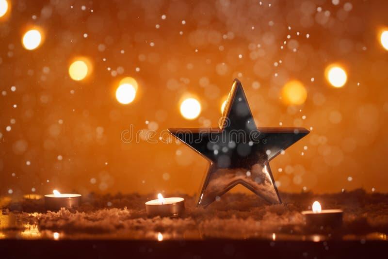 Kerstmisachtergrond met grote zilveren ster, kaarsen, sneeuw, bokeh lichten, het sneeuwen, Kerstmis stock fotografie