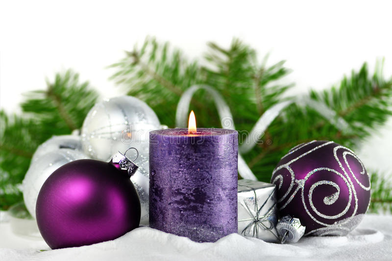Kerstmisachtergrond met kaars en decoratie Purpere en zilveren Kerstmisballen over sparrentakken in de sneeuw stock fotografie