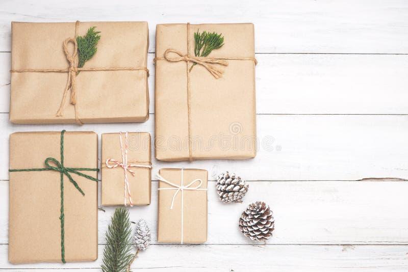 Kerstmisachtergrond met met de hand gemaakte huidige giftdozen en rustieke decoratie op witte houten raad royalty-vrije stock foto's