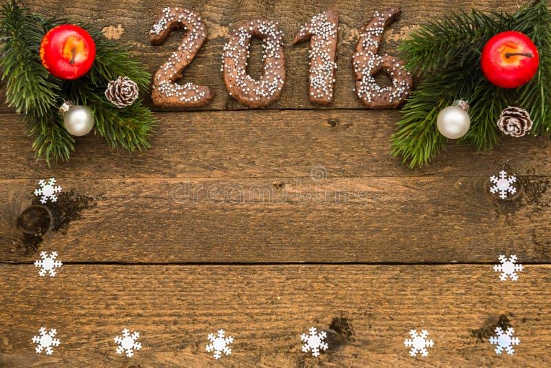 Kerstmisachtergrond met peperkoeknummer 2016, spartakken en decoratie met kader voor uw tekst op de oude houten raad stock foto's