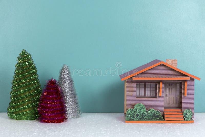 Kerstmisachtergrond met plattelandshuisje en speelgoedbomen stock fotografie