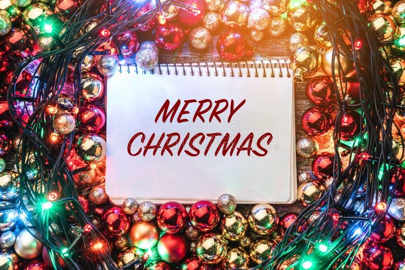 Kerstmisachtergrond met rode en gouden die snuisterijen, rond een notitieboekje voor Vrolijk Kerstmisbericht worden aangestoken H royalty-vrije stock foto's