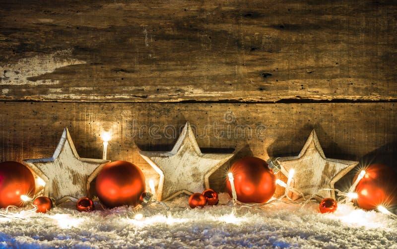 Kerstmisachtergrond met witte sterren, rode snuisterijen en lichten over sneeuw bij nacht stock afbeeldingen