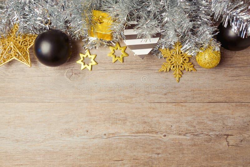 Kerstmisachtergrond met zwarte, gouden en zilveren decoratie op houten lijst Mening van hierboven met exemplaarruimte stock afbeeldingen