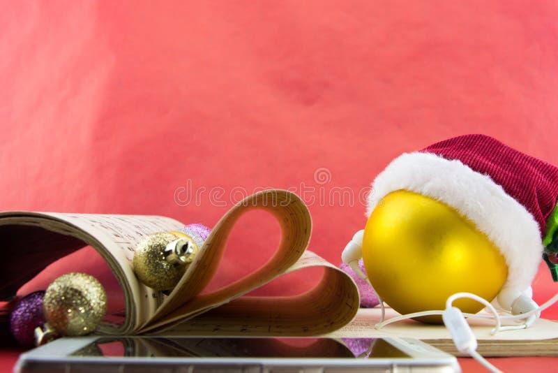 Kerstmisbal met de hoed van de Kerstman en oortelefoons, het boek van de muziekaantekening met pagina's die hart vormen stock afbeelding