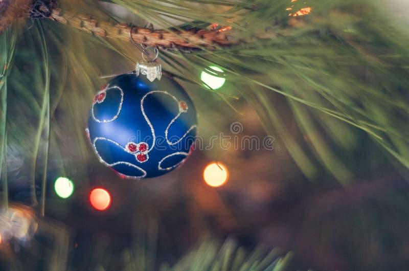 Kerstmisbal op een Kerstboomtak over vage glanzende achtergrond stock fotografie