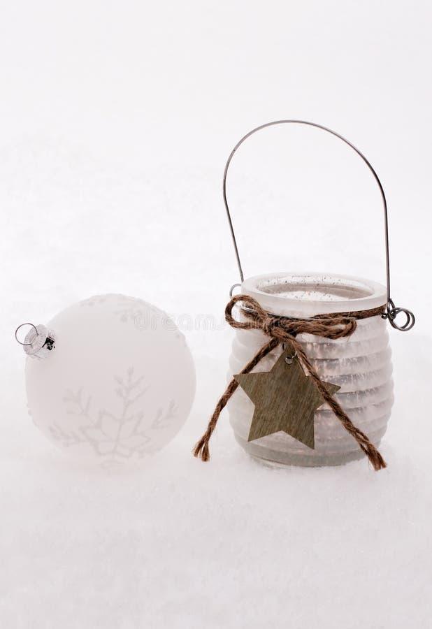 Kerstmisbal, windkaars met ster in sneeuw stock afbeelding