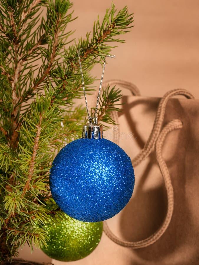 Kerstmisballen op kleine spar tegen giftzak stock afbeelding