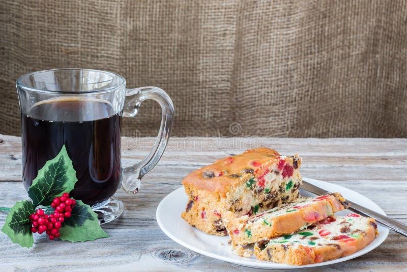 Kerstmisbeeld van plakken van fruitcake op plaat met kop van koffie royalty-vrije stock afbeeldingen