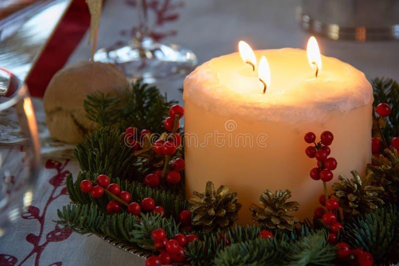 Kerstmisbelangrijkst voorwerp met grote kaars en rode bessen stock fotografie