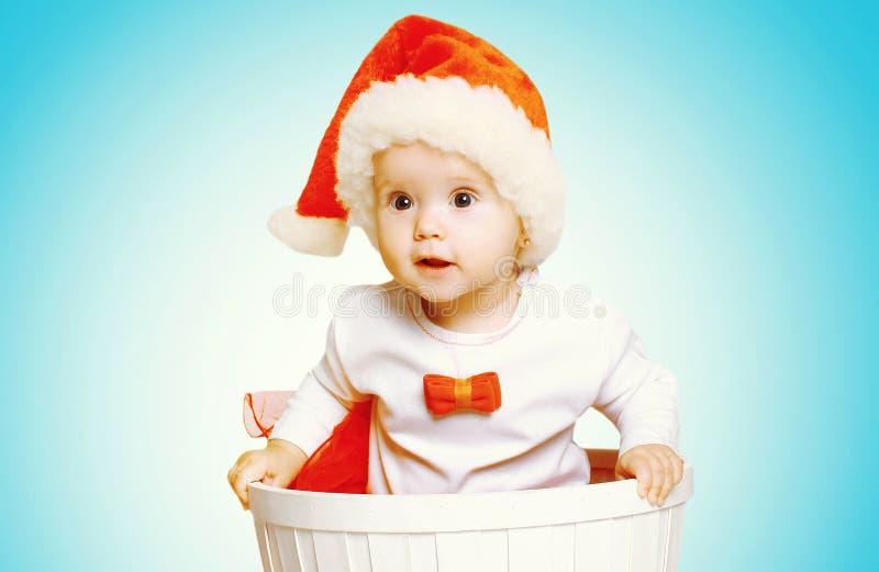 Kerstmisconcept - de mooie baby in santa rode hoed krijgt uit de container stock afbeelding