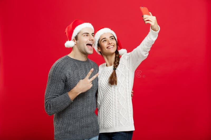 Kerstmisconcept - Jong aantrekkelijk paar die een selfie nemen door mobiele telefoon in Kerstmisdag te vieren stock afbeelding