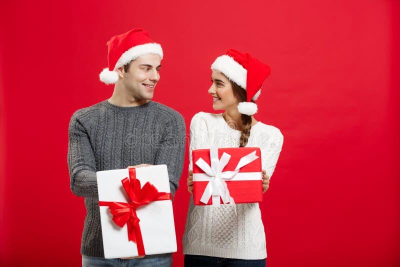 Kerstmisconcept - Jong aantrekkelijk paar die giften geven aan elkaar die in Kerstmisdag vieren royalty-vrije stock afbeeldingen