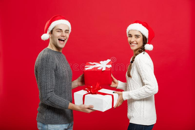 Kerstmisconcept - Jong aantrekkelijk paar die giften geven aan elkaar die in Kerstmisdag vieren royalty-vrije stock afbeelding
