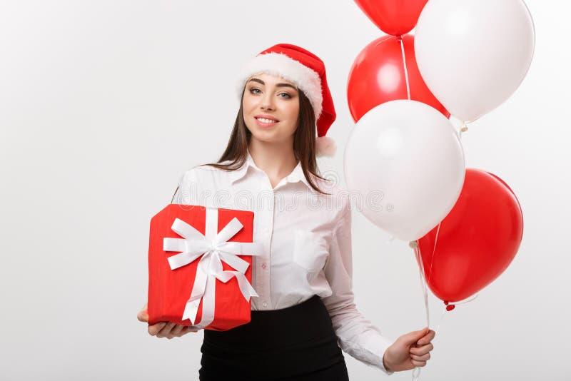 Kerstmisconcept - jonge gelukkige Kaukasische bedrijfsvrouw met het vakje van de de holdingsgift van de santahoed en ballon met e stock afbeelding