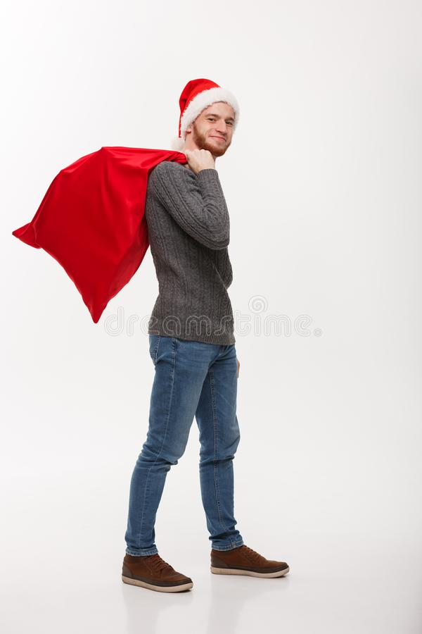 Kerstmisconcept - Jonge zekere slimme mens die rode grote santazak met heel wat binnen heden houden royalty-vrije stock afbeeldingen