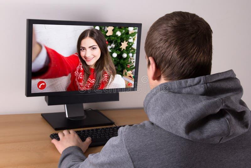 Kerstmisconcept - mens het videochatting met zijn meisje stock foto