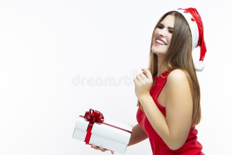 Kerstmisconcepten Lachend Kaukasisch Meisje in Rode Kleding en Santa Hat Houdend Uiterst kleine Witte die Giftdoos omhoog met roo royalty-vrije stock foto's