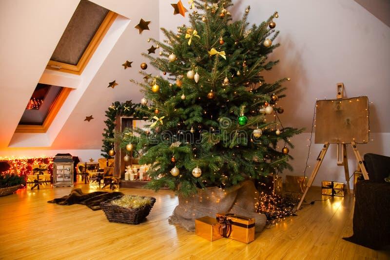 Kerstmisdecoratie in de studio, grote natuurlijke spar met gouden ballen, bogen en sneeuwvlokken, houten open haard en kaarsen  royalty-vrije stock afbeelding