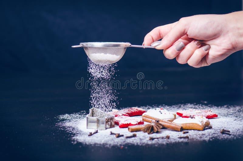 Kerstmisdecoratie en Koekjes Vrouwenhand die suiker op bestrooien koekjes Bloem en kruiden voor een baksel op een donkere backg stock foto's