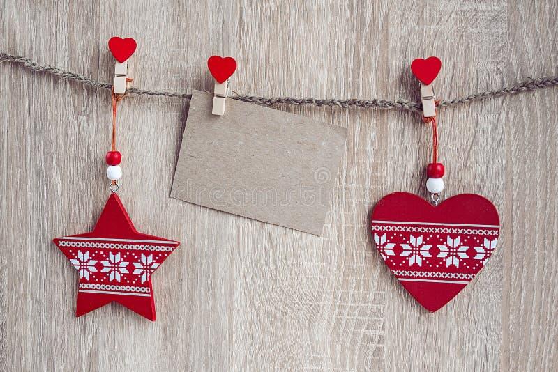 Kerstmisdecoratie met een lege kaart die over houten rug hangen stock afbeelding