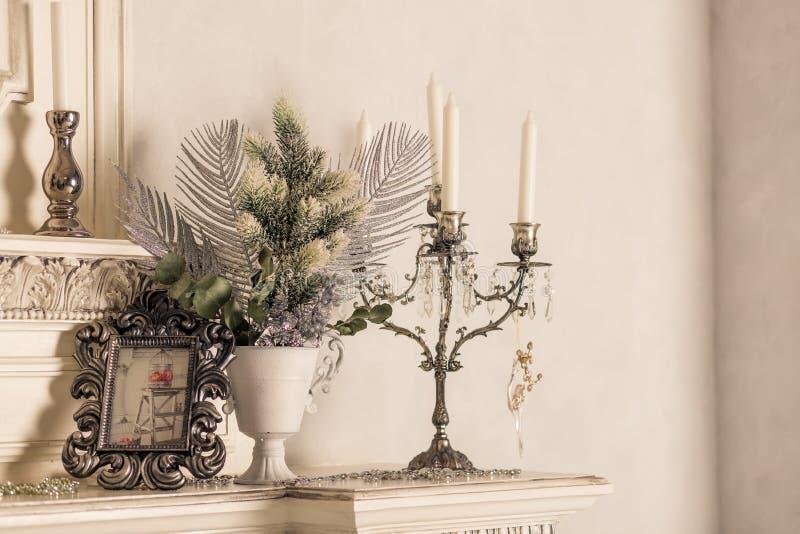 Kerstmisdecoratie met kaarsen op plank, witte muur Retro zilveren kandelaars met witte kaarsen Gestemd retro beeld royalty-vrije stock afbeeldingen