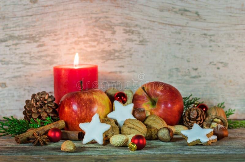 Kerstmisdecoratie met kaarslicht, sterkoekjes, rode appelen, noten en kruiden royalty-vrije stock foto