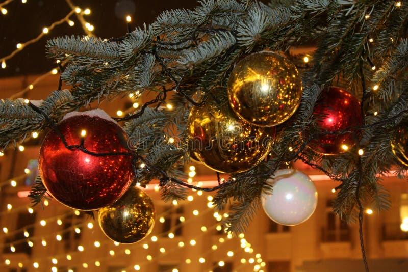 Kerstmisdecoratie op de Kerstboom in rode en gouden die kleuren met lichten, close-up worden uitgestrooid royalty-vrije stock afbeeldingen