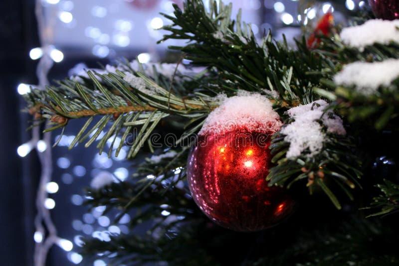 Kerstmisdecoratie op de Kerstboom in rode en gouden die kleuren met lichten, close-up worden uitgestrooid stock afbeeldingen