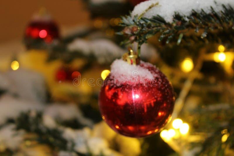Kerstmisdecoratie op de Kerstboom in rode en gouden die kleuren met lichten, close-up worden uitgestrooid stock afbeelding