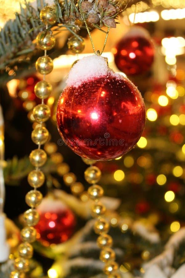 Kerstmisdecoratie op de Kerstboom in rode en gouden die kleuren met lichten, close-up worden uitgestrooid stock fotografie