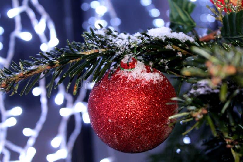 Kerstmisdecoratie op de Kerstboom in rode en gouden die kleuren met lichten, close-up worden uitgestrooid royalty-vrije stock afbeelding