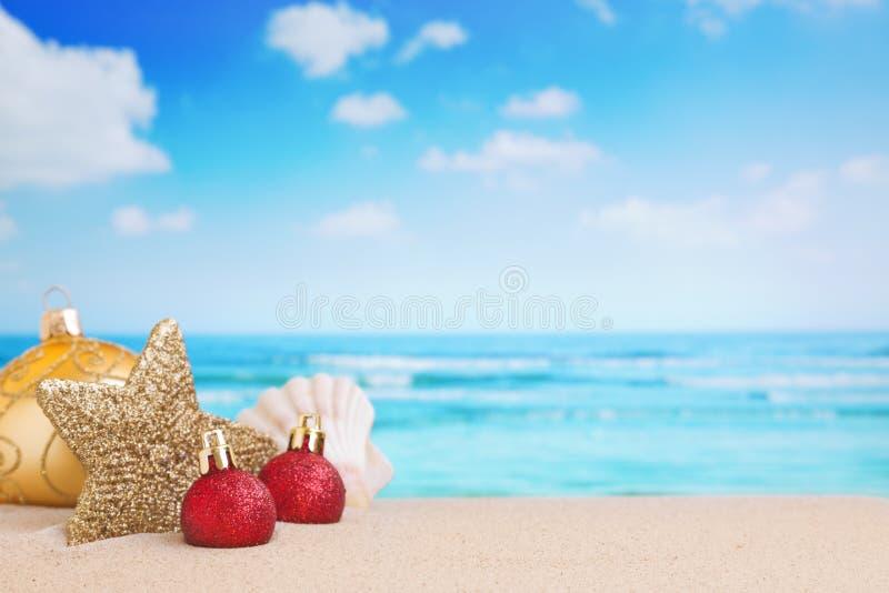 Kerstmisdecoratie op het strand, oceaan in de rug stock afbeeldingen
