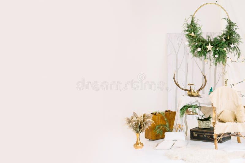Kerstmisdecoratie, rieten stoel met witte plaid, leerkoffers, in witte zaal in studio stock afbeelding