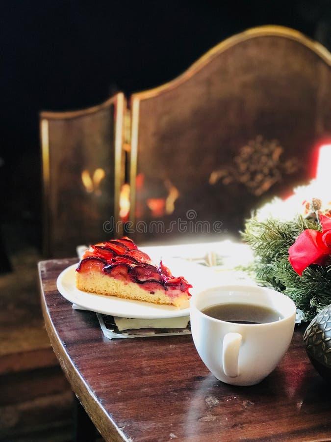 Kerstmisdecoratie voor Brandplaats met Damastpruim Plum Tart Cake en Koffie stock foto