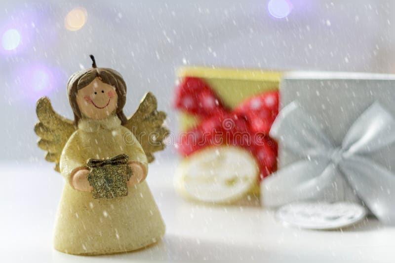 Kerstmisengel met giftdozen, Kerstmislichten op de achtergrond en de sneeuw royalty-vrije stock foto