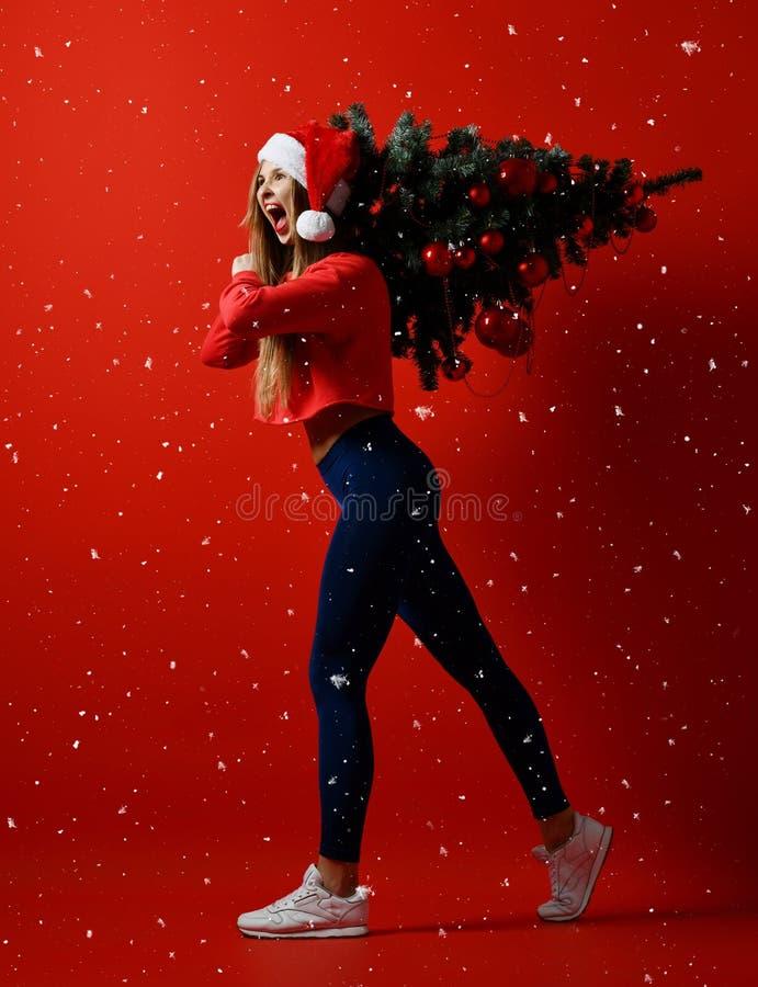 Kerstmisfitness sportvrouw die de boom van de holdingskerstmis van de santahoed op haar schouders dragen Sneeuwvlokken royalty-vrije stock afbeeldingen