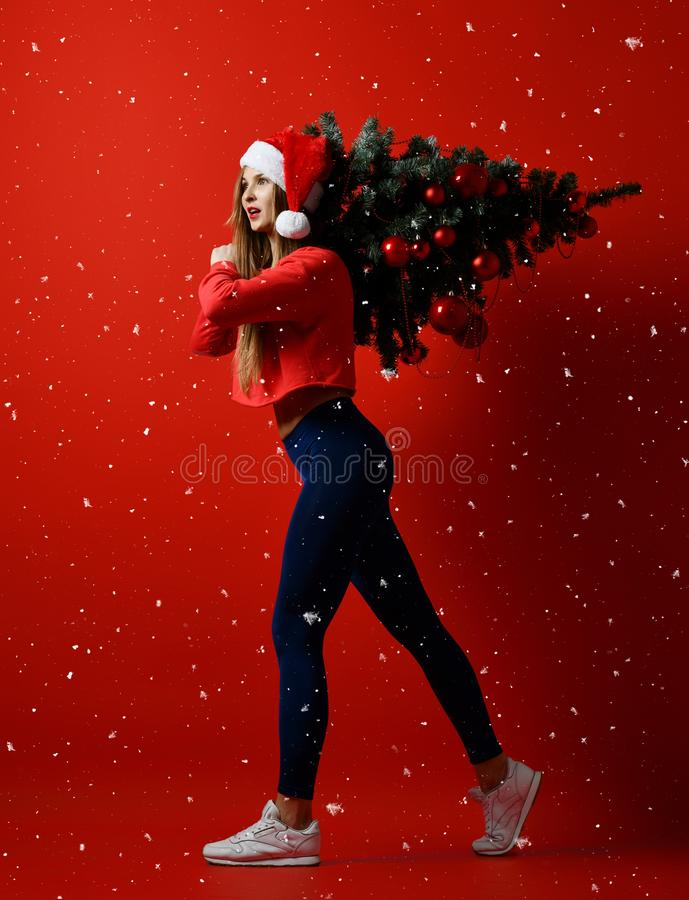 Kerstmisfitness sportvrouw die de boom van de holdingskerstmis van de santahoed op haar schouders dragen Sneeuwvlokken stock foto