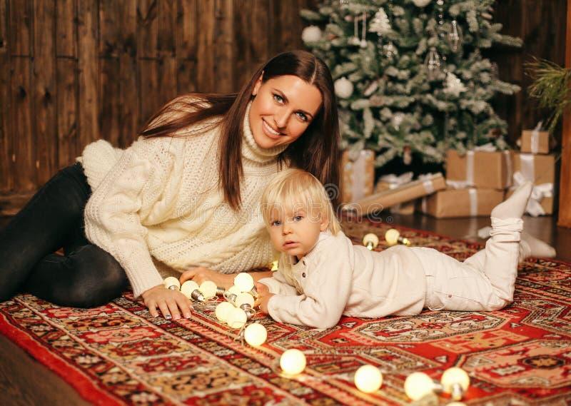 Kerstmisfoto van kleine leuke jongen en zijn mooie moederplayi stock afbeeldingen