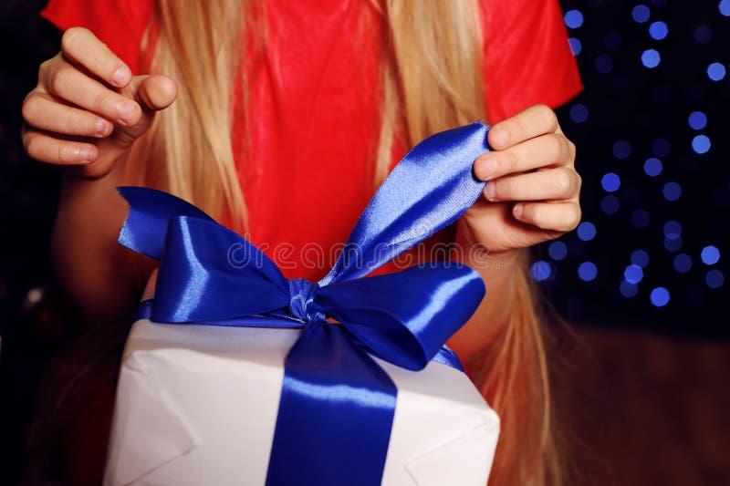 Kerstmisfoto van meisje in rode kleding die een witte gift houden - doos whith blauwe boog royalty-vrije stock foto