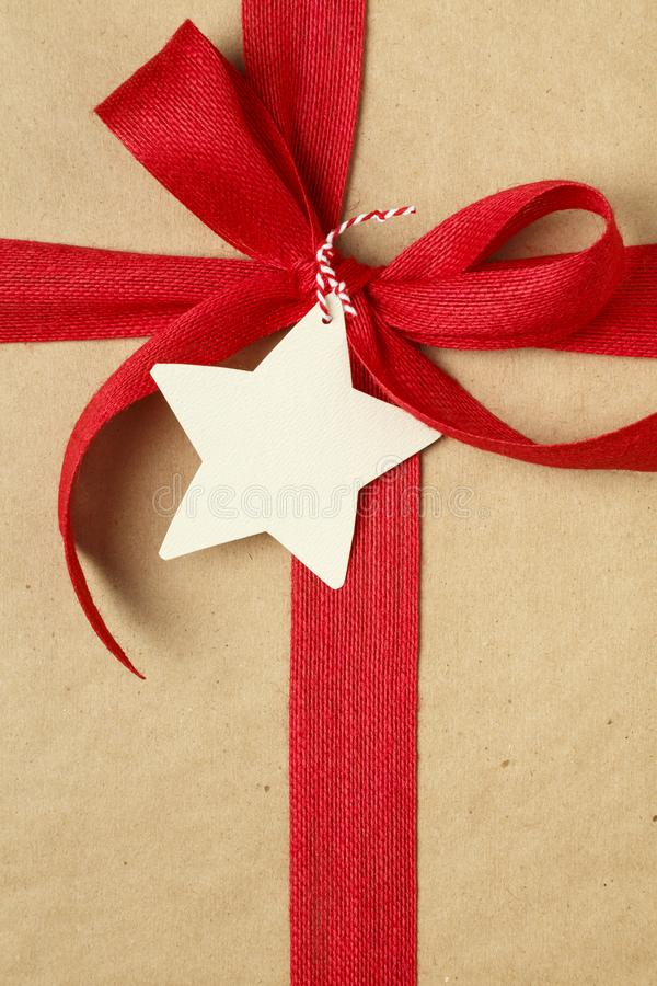 Kerstmisgift huidig met rode boog en lege giftmarkering Eenvoudige, gerecycleerde het verpakkende document van kraftpapier achter stock afbeeldingen