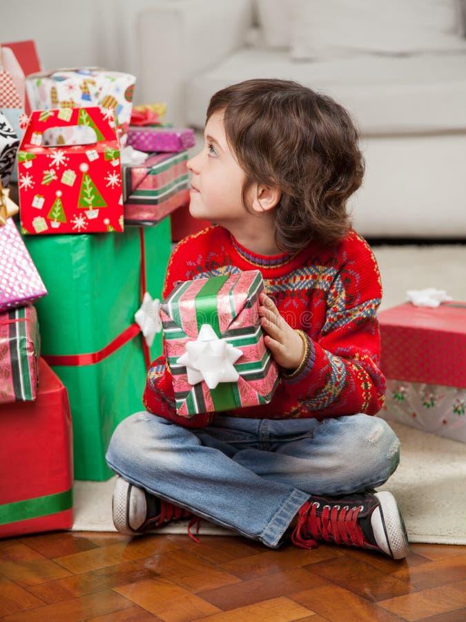 Kerstmisgift van de jongensholding terwijl het Zitten op Vloer stock afbeeldingen