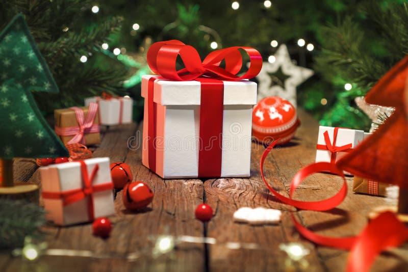 Kerstmisgiften en ornamenten op houten vloer, Kerstmislichten stock fotografie